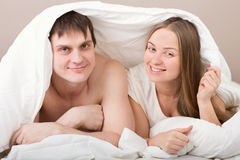 Portrait of happy young couple under blanket Royalty Free Stock Photo
