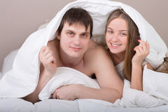 Portrait of happy young couple under blanket Royalty Free Stock Image
