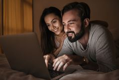 Portrait of a happy young couple using laptop. Computer while laying on bed at night time Stock Photos