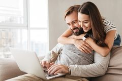 Portrait of a happy young couple using laptop computer. While hugging at home on a couch stock photo