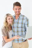 Portrait of happy young couple using laptop. Over white background Royalty Free Stock Images