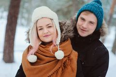 Portrait of happy young couple walking in winter snowy forest royalty free stock images