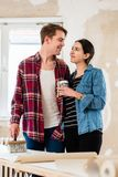 Portrait of a happy young couple holding tools for home remodeli Royalty Free Stock Photo