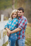 Portrait of happy young couple wearing shirts having fun outdoors near fence in park Royalty Free Stock Image