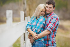 Portrait of happy young couple wearing shirts having fun outdoors near fence in park Stock Image