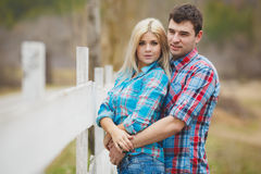 Portrait of happy young couple wearing shirts having fun outdoors near fence in park Stock Images