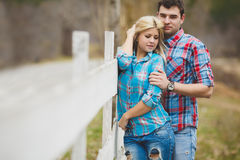 Portrait of happy young couple wearing shirts having fun outdoors near fence in park Royalty Free Stock Photography