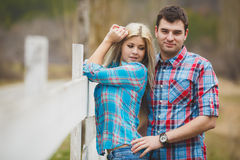 Portrait of happy young couple wearing shirts having fun outdoors near fence in park Stock Photos