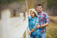 Portrait of happy young couple wearing shirts having fun outdoors near fence in park Royalty Free Stock Photos
