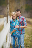 Portrait of happy young couple wearing shirts having fun outdoors near fence in park Stock Photo