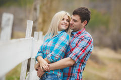 Portrait of happy young couple wearing shirts having fun outdoors near fence in park Stock Photography