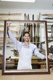 Portrait of a happy young craftsman holding big frame in workshop Royalty Free Stock Photo