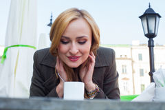 Portrait of happy young cute elegant woman sitting outdoor in a Stock Photos