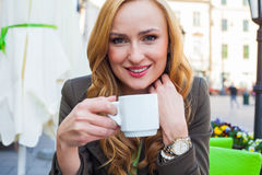 Portrait of happy young cute elegant woman sitting outdoor in a Royalty Free Stock Photo