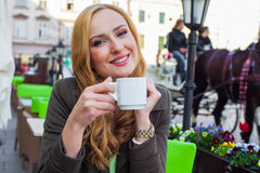 Portrait of happy young cute elegant woman sitting outdoor in a Stock Image