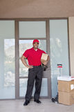 Portrait of a happy young delivery man standing with packages Royalty Free Stock Photos
