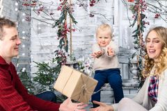 Portrait of happy young family at home. Man throwing a gift to h. Is wife, on the background his little pretty smiling son. Concept of Merry Christmas and New royalty free stock photos
