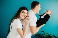 Portrait of a happy young family with a little baby boy. They are standing in the dining room near the turquoise wall and father is holding his son, mother is royalty free stock images
