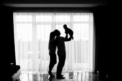 Portrait of a happy young family with a little baby boy. They are standing in the dining room near the window and father is holding his son stock photography