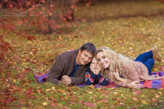 Portrait of a happy young family in park in the autumn Royalty Free Stock Image