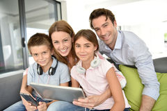 Portrait of happy young family sitting on sofa indoors Royalty Free Stock Images