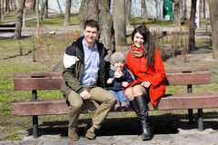 Portrait of happy young family spending time together in green nature in park. Royalty Free Stock Photos