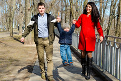 Portrait of happy young family spending time together in green nature in park. Stock Photography