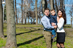 Portrait of happy young family spending time together in green nature in park. Royalty Free Stock Photography