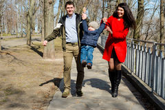 Portrait of happy young family spending time together in green nature in park. Stock Photos