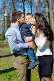 Portrait of happy young family spending time together in green nature in park. Royalty Free Stock Photo