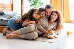 Portrait of a happy young family with two children and red fluffy cat royalty free stock image