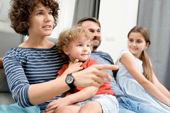 Family Watching TV. Portrait of happy young family with two children watching TV sitting on sofa in living room and discussing movies Stock Photo