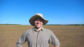 Portrait of happy young farmer in hat looking into the camera and smiling against the background of field and blue sky. Close up of handsome man in shirt stock video footage