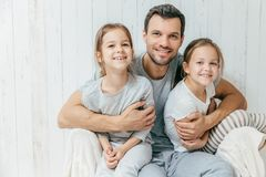 Portrait of happy young father embraces his two daughters, loves stock photo
