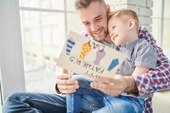 Father Hugging Son. Portrait of happy young father hugging cute son and celebrating Fathers day together sitting by window at home, copy space stock images