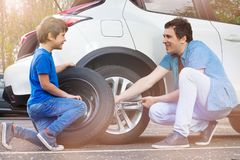 Happy father and son changing wheels on car stock photos