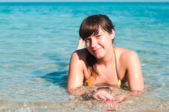 Happy young woman in bikini laying in sea Stock Image