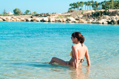 Young woman in bikini sitting on shoreline Stock Images