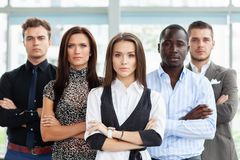 Portrait of a happy young female business leader standing in front of her team. stock photography