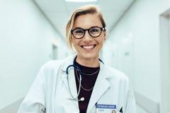 Female doctor standing in hospital corridor. Portrait of happy young female doctor standing in hospital corridor. Caucasian woman working in healthcare center royalty free stock photo