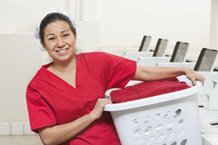 Portrait of a happy young female employee carrying laundry basket Stock Photography