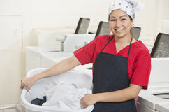 Portrait of a happy young female employee carrying laundry basket with washing machines in background Royalty Free Stock Photo
