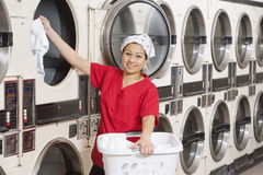 Portrait of a happy young female employee putting clothes in washer Royalty Free Stock Photos