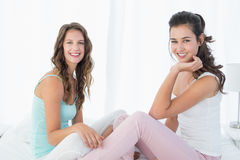 Portrait of happy young female friends on bed Royalty Free Stock Images
