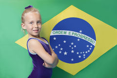 Portrait of a happy young female gymnast with arms crossed standing in front of South American flag Stock Photography