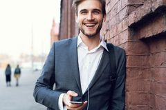 Portrait of a happy young formal dressed man leaning on a wall outdoors holding mobile phone. royalty free stock photo