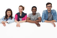 Portrait of happy young friends with blank board Stock Photo