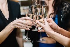 Group of partying girls clinking flutes with sparkling wine royalty free stock photos