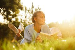 Portrait of a happy young girl with backpack. Laying on a grass at the park, reading a book Stock Image