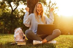 Portrait of a happy young girl with backpack. Sitting with legs crossed, using laptop computer, celebrating Stock Photography